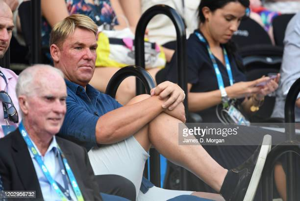 Ex-Australian cricketer Shane Warne watches the Semifinal match between Roger Federer of Switzerland and Novak Djokovic of Serbia on day eleven of...