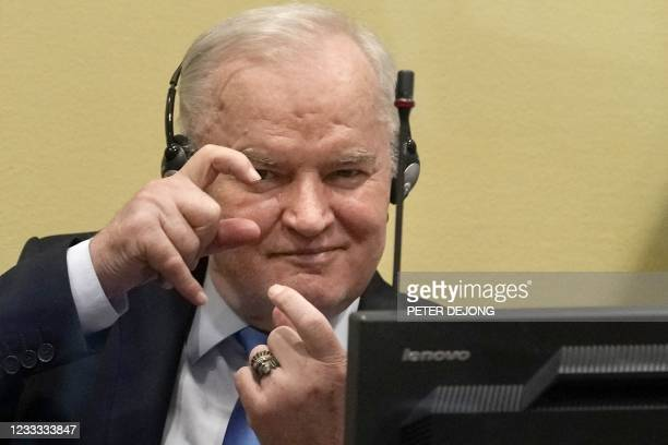 Ex-Bosnian Serb military chief Ratko Mladic imitates taking pictures as he sits in the defendant box prior to the hearing of the final verdict on...