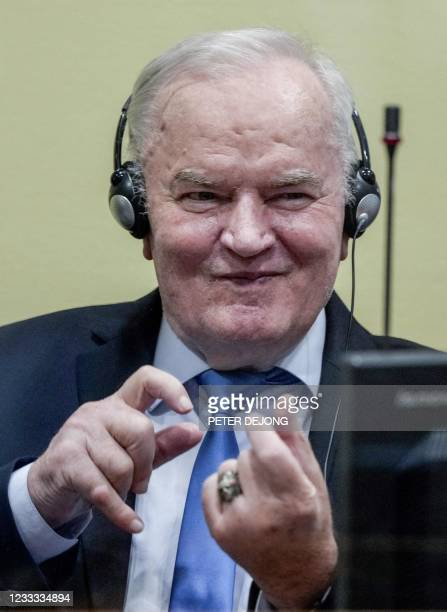 Ex-Bosnian Serb military chief Ratko Mladic imitates taking pictures from the defendant box during the earing of the final verdict on appeal against...