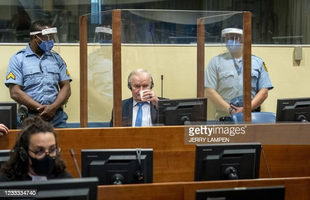 Ex-Bosnian Serb military chief Ratko Mladic looks on as he drinks from the defendant box during the earing of the final verdict on appeal against his...