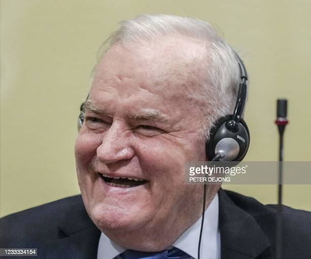 Ex-Bosnian Serb military chief Ratko Mladic smiles from the defendant box prior to the hearing of the final verdict on appeal against his genocide...