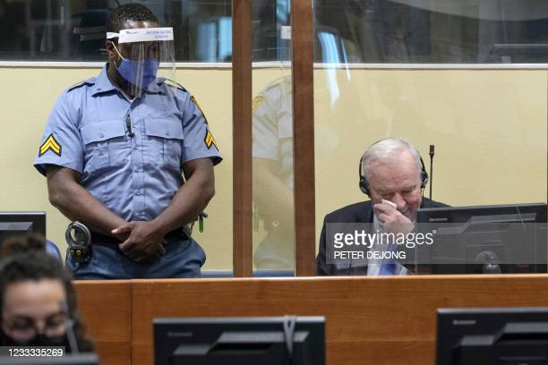 Ex-Bosnian Serb military chief Ratko Mladic wipes his face as he sits in the defendant box during the earing of the final verdict on appeal against...