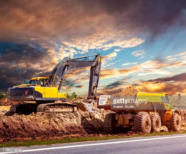 工事現場の掘削機とダンプトラック - ダンプカー ストックフォトと画像
