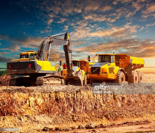 excavator and dump trucks on the construction site - dump truck stock pictures, royalty-free photos & images