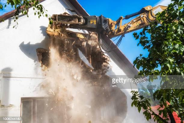 Excavator arm demolishing an old house