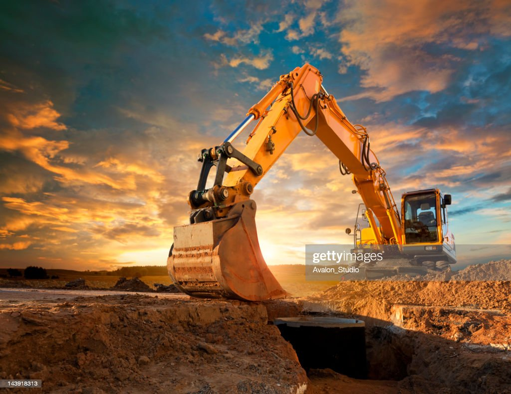 Excavator at a construction site against the setting sun. : Stock Photo