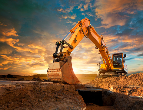 Excavator at a construction site against the setting sun. 143918313