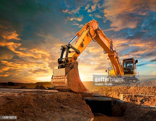 excavator at a construction site against the setting sun. - gruva bildbanksfoton och bilder