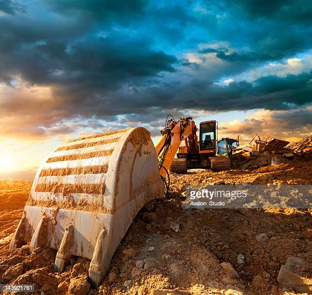Excavator at a construction site against the setting sun