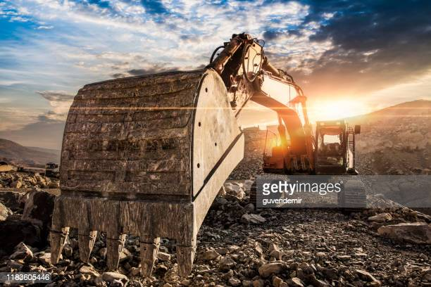 excavator at construction site against sunset - excavator stock pictures, royalty-free photos & images