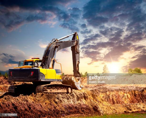 excavator at the construction site in the evening. - land mine stock pictures, royalty-free photos & images