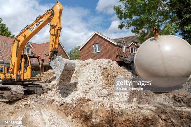 A Excavator crawler digging a trench for an underground tank on a housing development in Hampshire England UK