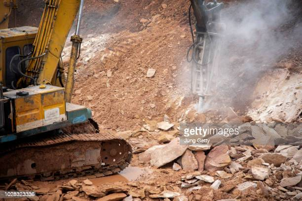 excavator drilling on top of rocks at foundation infrastructure construction site - archaeology stock pictures, royalty-free photos & images
