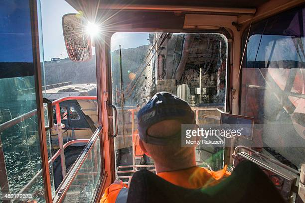 Excavator driver in digger cab at surface coal mine