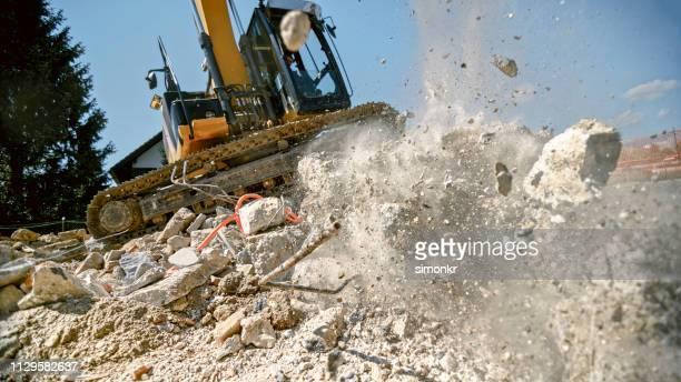 bagger greifer zerkleinern beton-block, in luft - baumaschine stock-fotos und bilder