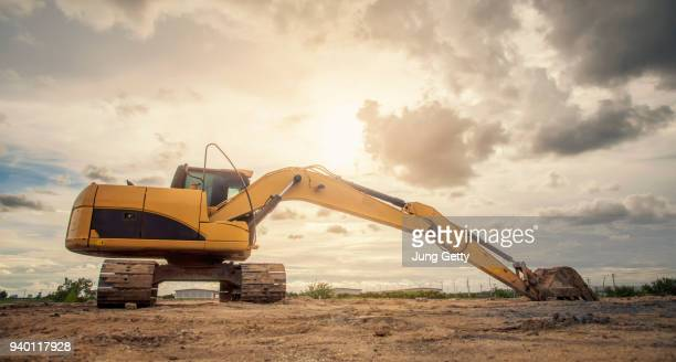 excavator heavy machine construction site on sunset sky background