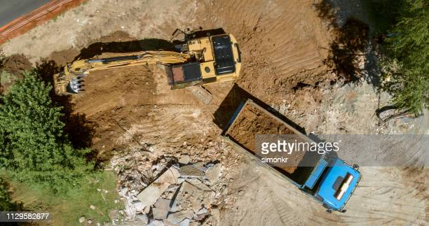 excavator loading dug out soil onto truck at building site - digging stock pictures, royalty-free photos & images