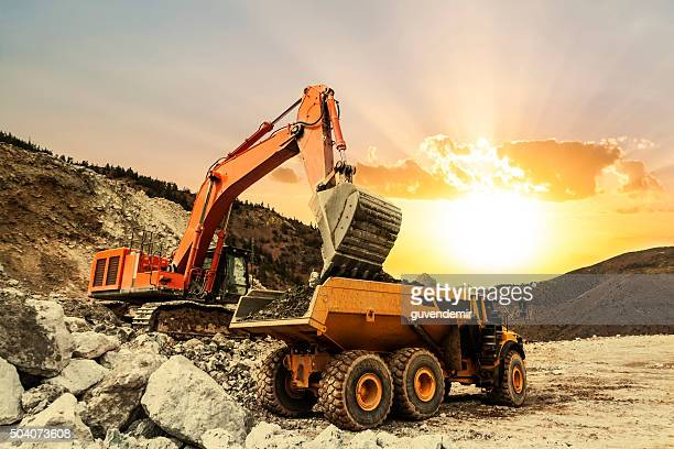 excavator loading dumper truck on mining site - excavator stock photos and pictures