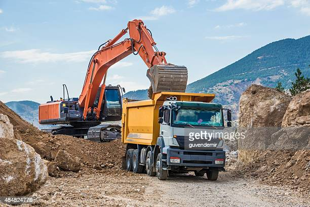 excavator loading dumper truck - dump truck stock pictures, royalty-free photos & images