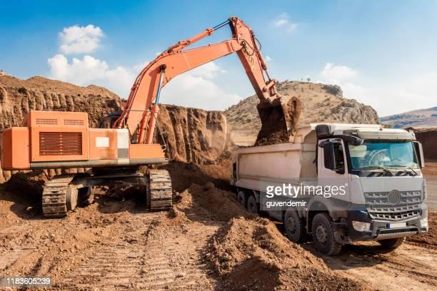 日没時にダンパートラックを積み込む掘削機 - ダンプカー ストックフォトと画像