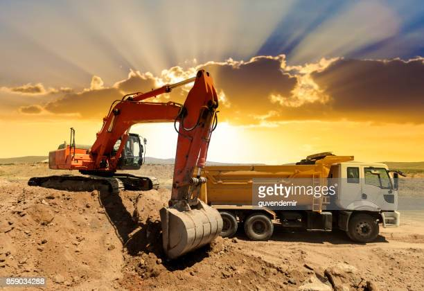 excavator loading dumper trucks at sunset - dump truck stock pictures, royalty-free photos & images