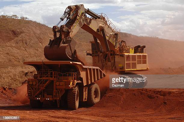 Excavator loading ore into a haul truck.