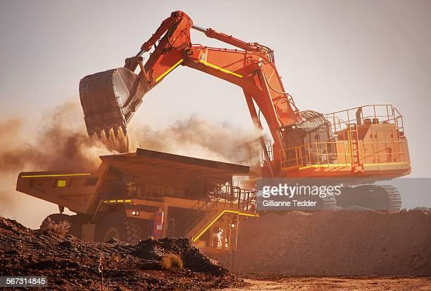 Excavator loads mine truck