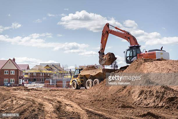 excavator moving earth on housing building site - housing development stock pictures, royalty-free photos & images