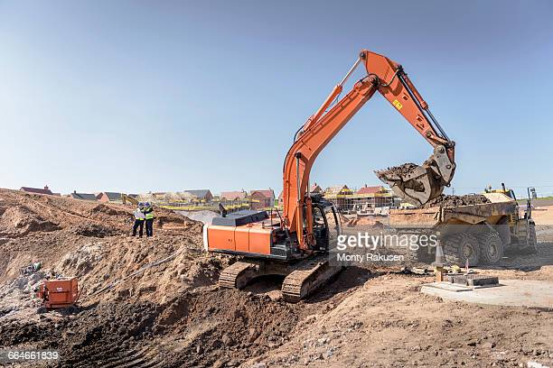 Excavator moving earth on housing building site