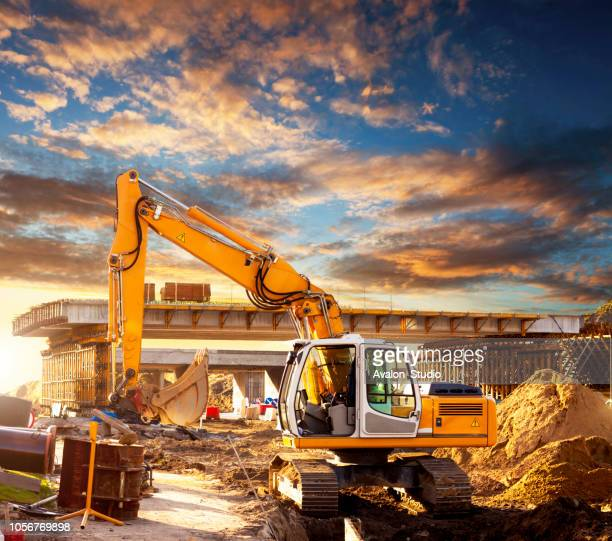 excavator on a road construction site - caterpillar stock pictures, royalty-free photos & images