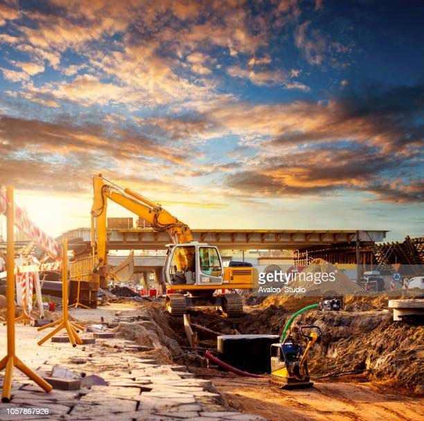 excavator on a road construction site - construction industry stock pictures, royalty-free photos & images