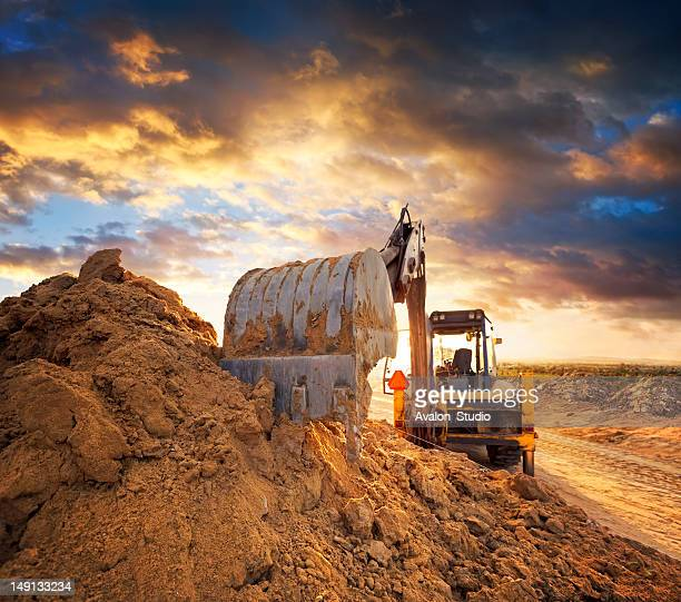 Excavator on the construction site of the road against the setting sun