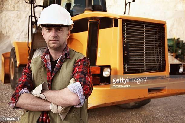 excavator operator in front of his vehicle
