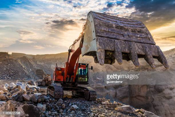 excavator working at mining site - coal mine stock pictures, royalty-free photos & images