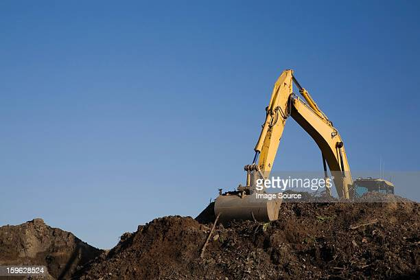 Excavator working on pile of topsoil