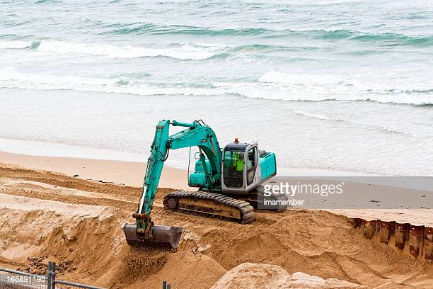 Excavator working on the beach with ocean, copy space
