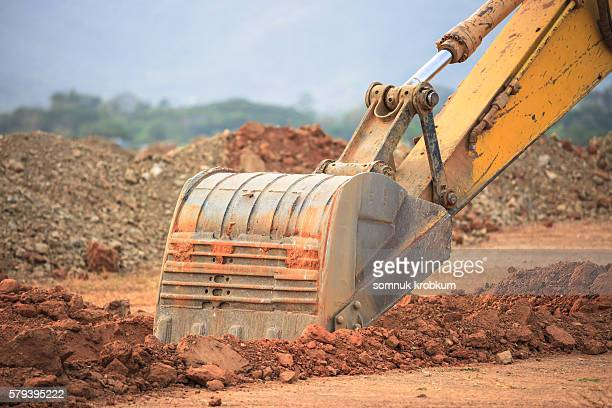 Excavator working with red soil and dusty.