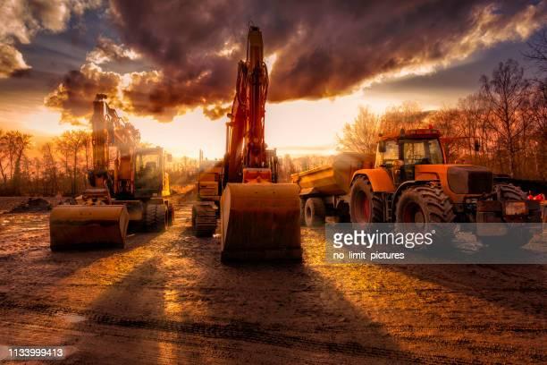 建設現場の掘削機とトラック - 建設用機器 ストックフォトと画像