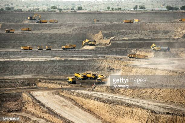 Excavators and dump trucks excavate sand and rocks from an open pit mine at the Sindh Engro Coal Mining Co site in the Thar desert Pakistan on...
