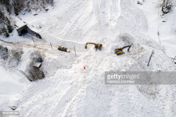 TOPSHOT Excavators remove the snow on the site of an avalanche that covered the railway of the Brig Visp Zermatt Bahn company between Visp and Taesch...
