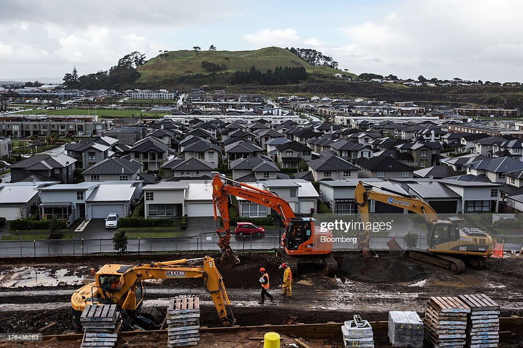 Excavators stand on a construction site in front of houses in the suburb of Mount Wellington in Auckland, New Zealand, on Monday, Aug. 12, 2013. New Zealand's growth rate is forecast to outpace Australia's for the next two years, helping stem an exodus that's resulted in the highest proportion of its people living overseas in the developed world after Ireland. Photographer: Brendon O'Hagan/Bloomberg via Getty Images