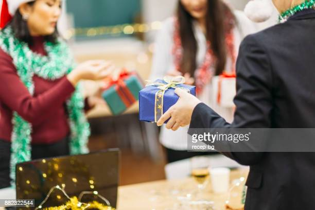 exchanging christmas gifts - work party stock pictures, royalty-free photos & images