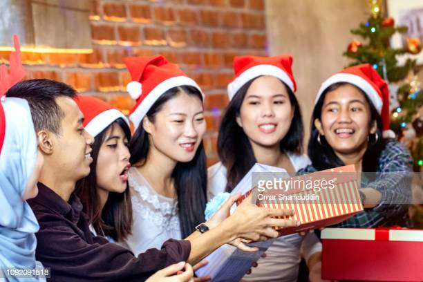 Exchanging gifts during Christmas gathering with friends