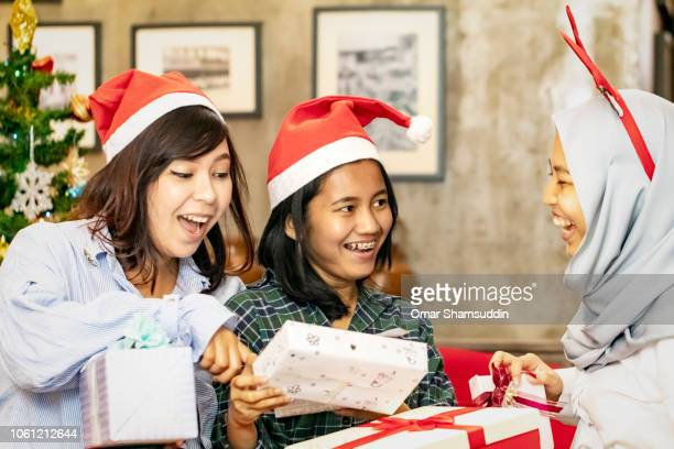 Exchanging gifts with friends during Christmas celebration with friends