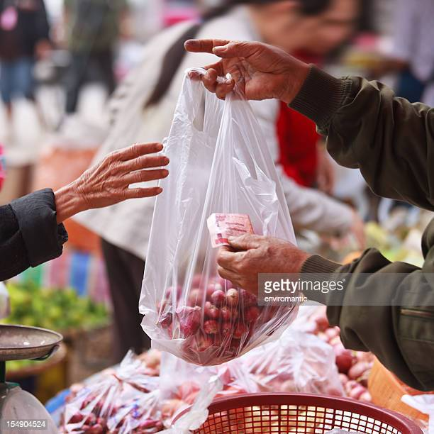 Exchanging money for vegetables in a Thai market.