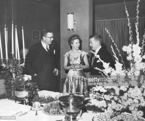 Exchanging party chatter at a recent gathering at the Denver Country club are Mr and Mrs Van Holt Garrett Jr and Thomas O'Rourke Mrs Garrett's frock...