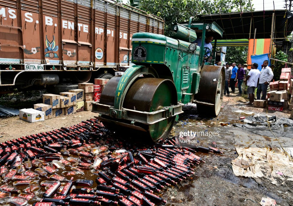 Excise Minister of Assam, Parimal Suklabaidya driving a road roller over seized liquor under the supervision of team of officials and under the aegis of Assam Excise and police at Garchuk in Guwahati, Assam, India on Friday, August 10, 2018.
