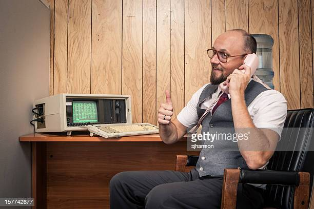 excited 1980's computer worker nerd  on phone at cubicle