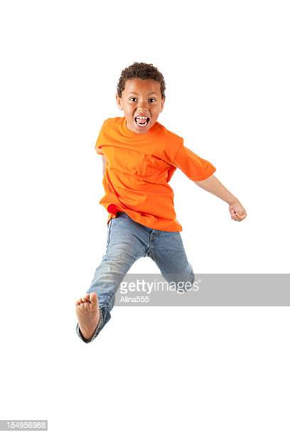 Excited 8-year old mixed race boy jumping on white