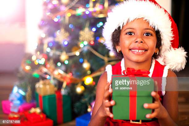 Excited African American child holding wrapped Christmas present